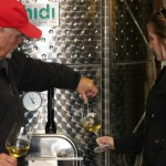 Bob Schroth gives Carrie Smith a taste of the 2010 Chardonnay, aged in 100 percent French Oak. The wine in the tank is about to be bottled and will be released in December.