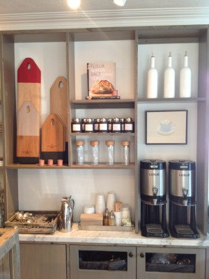 """The artful arrangement of retail goods and coffee fixings. Color blocked cutting boards by Lostine neighbors """"Flour Water Salt Yeast,"""" a home baker's guide to artisanal bread-making. Fittingly, a Mike Piggott cappuccino presides over it all."""